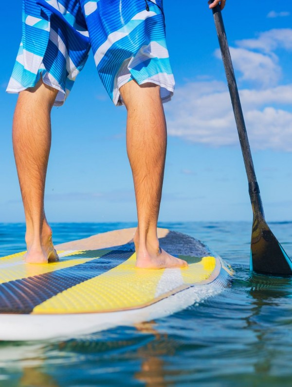 22168290 - young attractive mann on stand up paddle board, sup, in the blue waters off hawaii