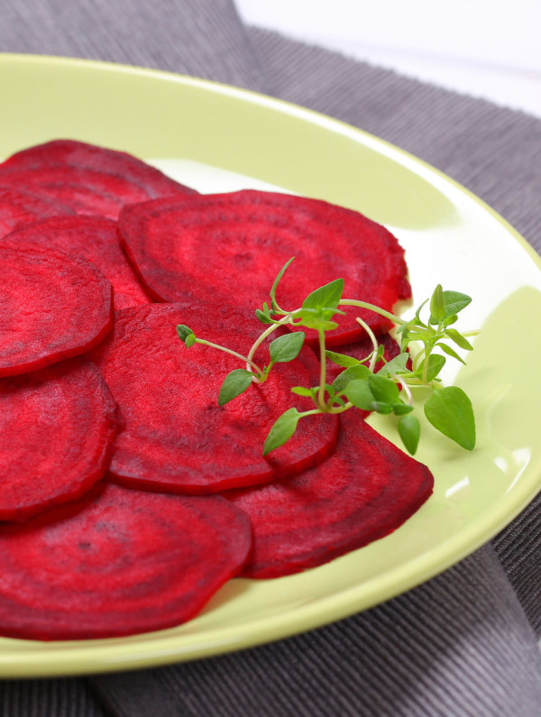 81224805 - plate of thin beetroot slices on grey place mat - close up