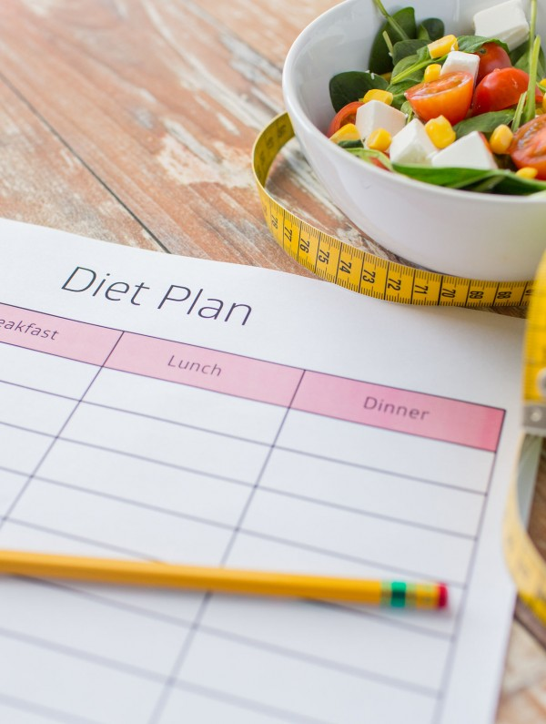 41729367 - healthy eating, dieting, slimming and weigh loss concept - close up of diet plan paper green apple, measuring tape and salad