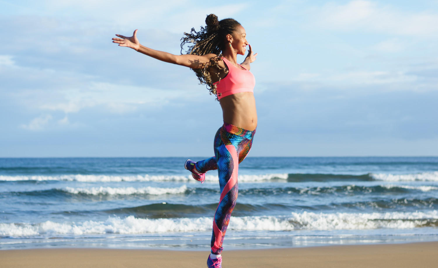 Sporty woman dancing and jumping at the beach.