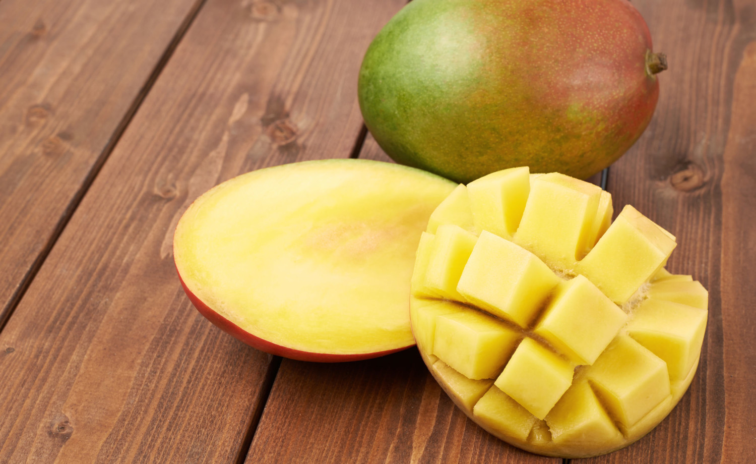 Ripe mango fruit lying over the brown colored wooden board surface as a background composition