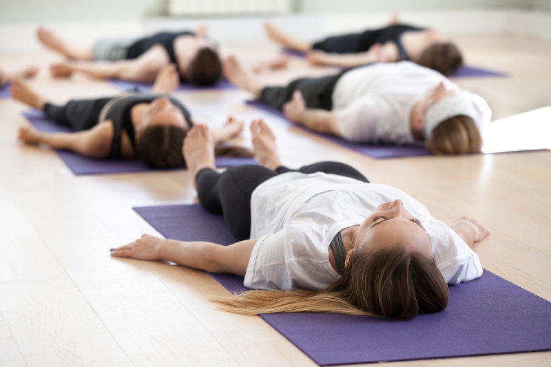 Group of young sporty people practicing yoga lesson, doing Savasana, Dead Body pose, Corpse exercise, working out, indoor full length, students training in sport club, studio